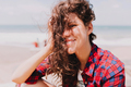 Portrait of stylish pretty young lady with dark wavy hair and beautiful eyes sitting by the ocean - PhotoDune Item for Sale