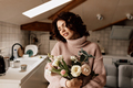 Charming stylish girl with curls wearing soft sweater holding bouquet of flowers - PhotoDune Item for Sale