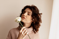 Wonderful stylish girl with curly hair wearing sweater holding flower and posing over light wall - PhotoDune Item for Sale