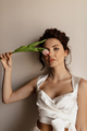 Stylish woman wearing white top holding tulip near the face and posing at camera - PhotoDune Item for Sale
