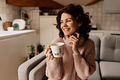 Lovable happy girl with curls wearing sweater holding a cup and enjoying warm day in the kitchen - PhotoDune Item for Sale