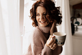 Happy charming girl with short wavy hairstyle drinking tea near the window and enjoying weekend time - PhotoDune Item for Sale