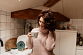 Adorable charming girl with short curly hair in soft sweater drinking tea and smiling in kitchen - PhotoDune Item for Sale