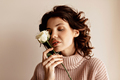 Incredible stylish woman with curly hair wearing soft pink sweater holding flower and smiling - PhotoDune Item for Sale