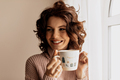 Charming adorable lady with curls holding a cup and looking aside near the window in sunny warm day - PhotoDune Item for Sale