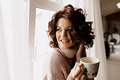 Close up portrait of adorable gentle woman with short curly hair in soft sweater drinking tea - PhotoDune Item for Sale