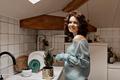 Incredible stylish lovely woman with curls in knitted sweater is transplanting pots in the kitchen - PhotoDune Item for Sale