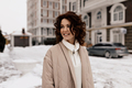 Charming pretty lady with curly hair wearing beige coat walking down the street with happy smile - PhotoDune Item for Sale