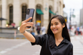 Asian businesswoman influencer outdoors in city street using mobile phone while vlogging or taking - PhotoDune Item for Sale