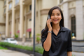 Happy Asian businesswoman outdoors in city street talking on phone while smiling and walking - PhotoDune Item for Sale
