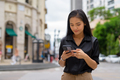 Asian businesswoman outdoors in city street using mobile phone while texting - PhotoDune Item for Sale