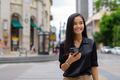 Asian businesswoman outdoors in city street using mobile phone while walking and smiling - PhotoDune Item for Sale