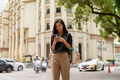 Happy Asian businesswoman outdoors in city street using mobile phone while texting - PhotoDune Item for Sale