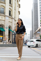 Beautiful Asian businesswoman smiling and talking on phone outdoors in city street while walking - PhotoDune Item for Sale