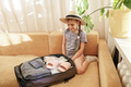 Girl sitting near suitcase packed for vacation and demonstrates the vaccination proof message - PhotoDune Item for Sale
