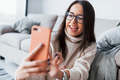 Making selfie. Young beautiful woman in glasses sitting at home alone with phone in hands - PhotoDune Item for Sale