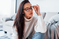 Young beautiful woman in casual clothes and in glasses sitting at home alone - PhotoDune Item for Sale