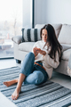 Young beautiful woman in casual clothes sitting at home alone with phone in hands - PhotoDune Item for Sale