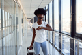 Young african american female passanger in casual clothes is in airport with baggage checking time - PhotoDune Item for Sale