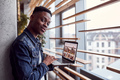 Young positive african american guy standing indoors with laptop in hands - PhotoDune Item for Sale