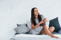 Young beautiful woman in casual clothes sitting at home alone on the bed - PhotoDune Item for Sale