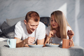 Young lovely couple have a breakfast at home while lying down on bed - PhotoDune Item for Sale