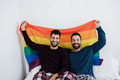 Gay male couple holding lgbt rainbow flag indoors on bed at home - Main focus on left man face - PhotoDune Item for Sale