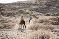 Young couple riding horses doing excursion at sunset - Main focus on woman back - PhotoDune Item for Sale