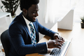 Business african man working inside modern office using computer laptop - Focus on face - PhotoDune Item for Sale