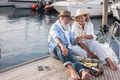 Senior couple cheering with champagne on sailboat during summer vacation - Focus on faces - PhotoDune Item for Sale