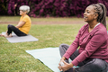 Senior people doing yoga class keeping distance at city park - Focus on african woman face - PhotoDune Item for Sale