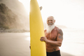 Senior surfer man holding surf board on the beach at sunset - Focus on face - PhotoDune Item for Sale