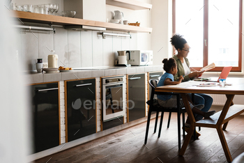 Black mother drawing with her daughter at table in home kitchen