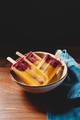 Fruit homemade popsicles made are from fresh mango, blackcurrant and coconut milk. - PhotoDune Item for Sale