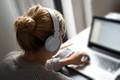 blonde woman with headphones working on notebook computer - PhotoDune Item for Sale