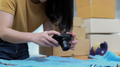 Young woman uses a camera to take pictures of products to post them for sale online. - PhotoDune Item for Sale