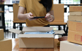 A woman selling an online product uses a smartphone to take a picture of the product in the box. - PhotoDune Item for Sale