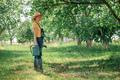 Female farmer with watering can in organic orchard - PhotoDune Item for Sale
