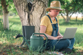 Female farmer using laptop computer in walnut orchard, innovative technology in organic farming - PhotoDune Item for Sale