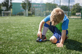 Young soccer player looks at the boots torn during the game on football field, hard training, sport - PhotoDune Item for Sale
