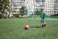 Little boy in blue and green form playing football on open field in the yard, a young soccer player - PhotoDune Item for Sale