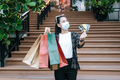 Pretty woman in mask holding shopping bag on stair - PhotoDune Item for Sale