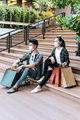 Cheerful Young couple holding multiple shopping paper bag at mall - PhotoDune Item for Sale