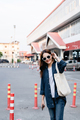 Pretty tourist wearing sunglasses carrying  big bag and smiling - PhotoDune Item for Sale