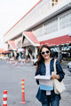 Pretty tourist wearing sunglasses holding paper map and smile - PhotoDune Item for Sale
