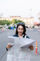 Young tourist female holding paper map looking with happy - PhotoDune Item for Sale