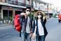 Young backpacker couple keep distance  thump down on city street - PhotoDune Item for Sale