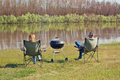 Man and women are sitting on a shore of river and making barbecue. - PhotoDune Item for Sale