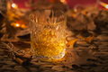 Whiskey, brandy or liquor, spices and autumn decorations on dark background - PhotoDune Item for Sale