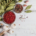 Black, red and white peppercorns, dried bay laurel leaves and garlic on white wooden background. - PhotoDune Item for Sale